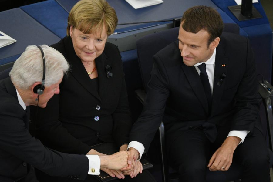 Bill Clinton ściska dłoń Emmanuela Macrona, między nimi Angela Merkel