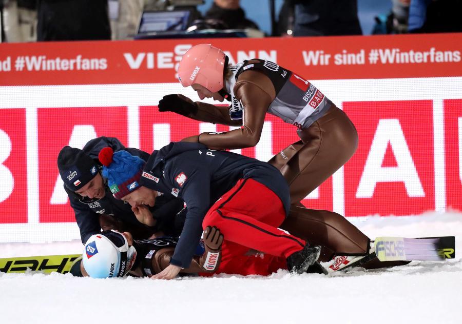 Piotr Żyła (L), Dawid Kubacki (P) i Stefan Hula (C), cieszą się ze zwycięstwa Kamila Stocha (dół) w czwartym konkursie Turnieju Czterech Skoczni w Bischofshofen