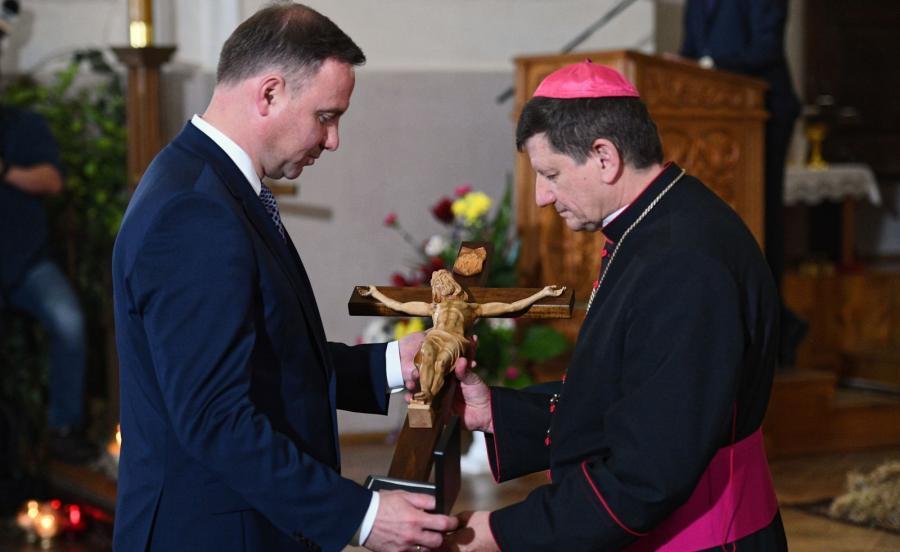 Prezydent Andrzej Duda (L) przekazuje na ręce ordynariusza diecezji łuckiej biskupa Witalija Skomarowskiego (P) pamiątkowy krzyż poświęcony pamięci pomordowanych Polaków