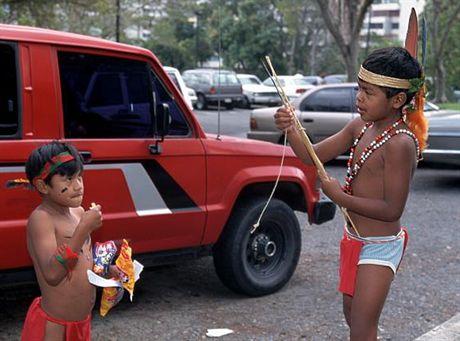 08 Feb 1996, Caracas, Venezuela --- Young boys of the Pemon tribe play and eat in a parking lot at the Conferencia Episcopal Venezolana, the Venezuelan synod organizing Pope John Paul II\'s visit to Venezuela. Caracas, Venezuela. --- Image by © Pablo Corral V/CORBIS