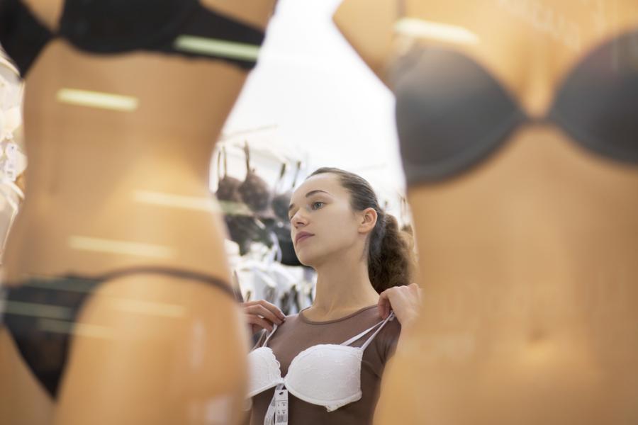 Kobieta mierząca biustonosz w sklepie