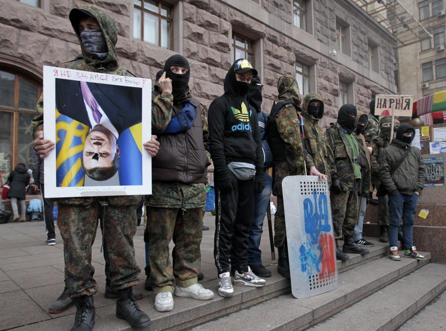 Wiktor Janukowycz do góry nogami. Protestujący na Majdanie trzymają portret prezydenta Ukrainy