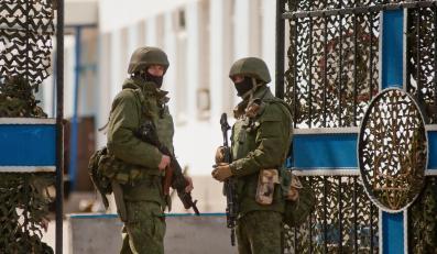 Sewastopol na Krymie. Uzbrojeni mężczyźni w mundurach przed ukraińską jednostką wojskową