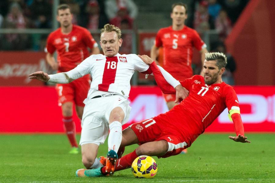 W pojedynku o piłkę gracz reprezentacji Polski Sebastian Mila (L) i Szwajcar Valon Behrami (C) w towarzyskim meczu piłkarskim we Wrocławiu