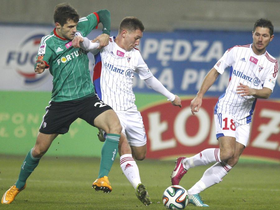 W pojedynku o piłkę Łukasz Broź (L) z Legii Warszawa i Mateusz Zachara (C) z miejscowego Górnika w meczu T-Mobile Ekstraklasy, rozegranym w Zabrzu