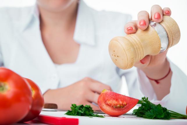 Kobieta soląca pomidory