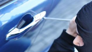 Złodziej włamuje się do samochodu