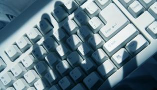 Klawiatura komputera i cień dłoni - zdjęcie ilustracyjne