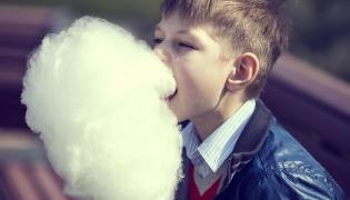 Chłopiec je watę cukrową
