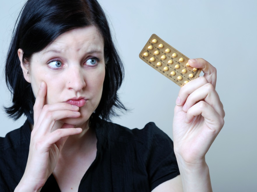 Kobieta trzymająca tabletki antykoncepcyjne