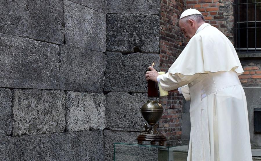Papież Franciszek zapala świecę przy Ścianie Śmierci