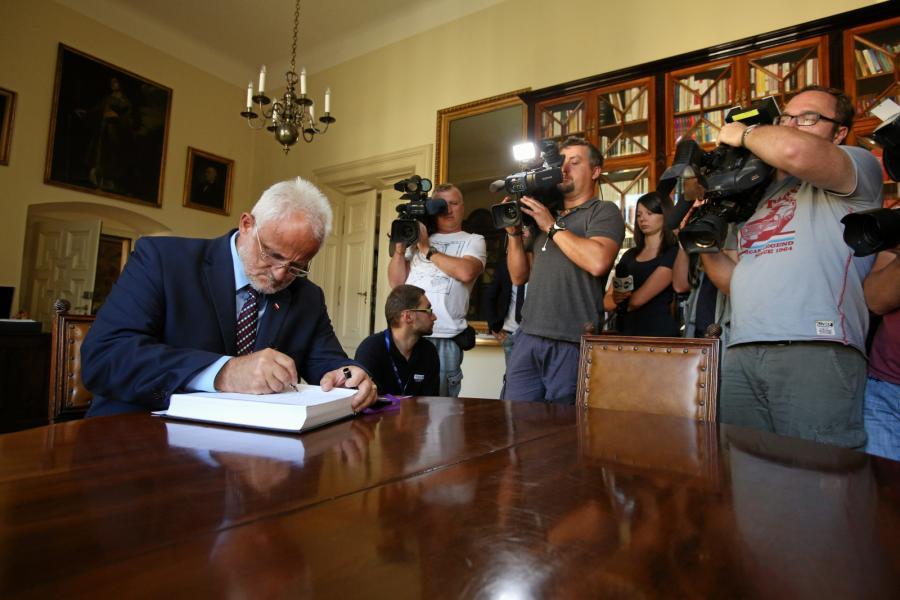 Wojewoda małopolski Józef Pilch wpisuje się do księgi kondolencyjnej wyłożonej w Pałacu Arcybiskupów Krakowskich