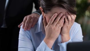 Kobieta płacze w biurze przy komputerze