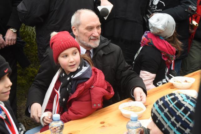 Minister obrony narodowej Antoni Macierewicz siedzi przy stole z najmłodszymi uczestnikami biegu - dla wszystkich chętnych kuchnia polowa przygotowała gorącą grochówkę.